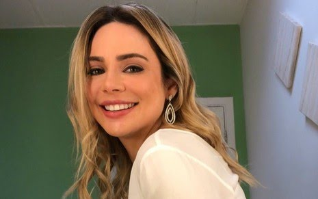 Rachel Sheherazade sorrindo, de lado, em um ambiente de parede verde